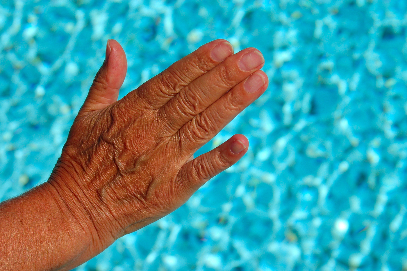 an old wrinkled female caucasian hand touching the fresh sparkling water of a swimming-pool